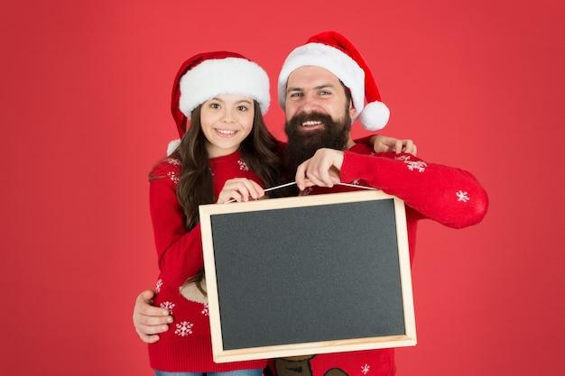 サンタクロースと一緒にクリスマスと新年を祝いましょう。幸せな家族は空の黒板を持っています。サンタと父と娘は赤い背景に見えます。サンタスクール。サンタパーティーに参加して、スペースをコピーしてください。