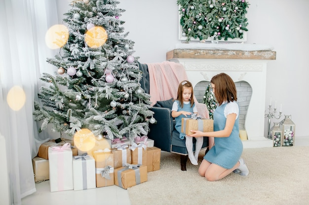 Celebrate christmas, emotions, feelings, precious moments. mom and daughter are laying out a welcome gift near the new year tree