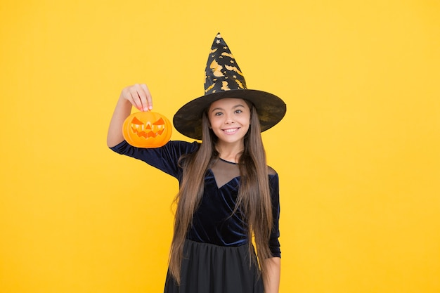 Celebrate the holidays. jack o lantern. halloween witch girl. happy childhood. teenage child in witch hat. cheerful kid holding pumpkin. carnival costume party. trick or treat. monster of a sale.