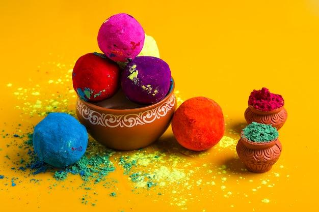 Отмечайте индийский фестиваль холи, многоцветный шар на желтой поверхности