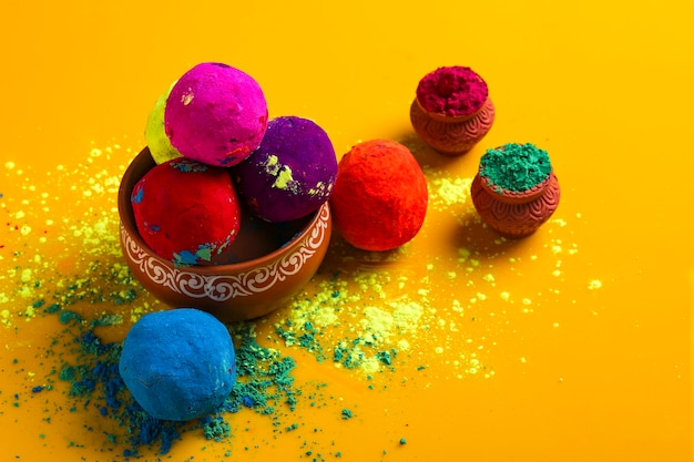 Celebrate indian festival holi, multicolors ball on yellow surface