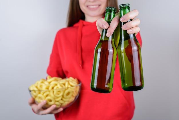パーティーの友達のコンセプトを祝います。手に2本のボトルを保持している陽気な嬉しいクールな楽観的な興奮した女性のトリミングされたクローズアップ写真の肖像画孤立した灰色の背景