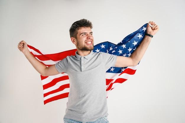 独立記念日を祝います。星条旗。白いスタジオの壁に隔離されたアメリカ合衆国の旗を持つ若い男。彼の国の愛国者として、夢中になって幸せで誇りに思っているように見えます。