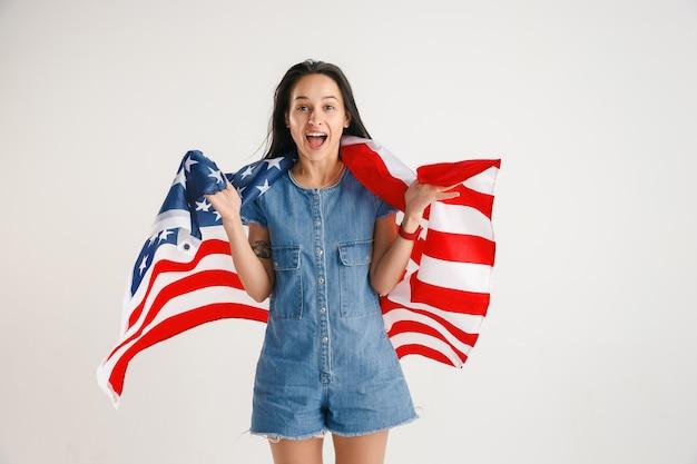 独立記念日を祝います。星条旗。白いスタジオの壁に隔離されたアメリカ合衆国の旗を持つ若い女性。彼女の国の愛国者として、夢中になって幸せで誇りに思っているように見えます。