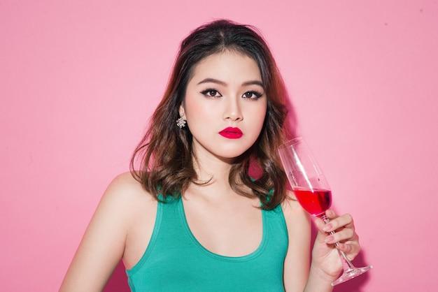 Празднование азиатской девушки с профессиональным макияжем и стильной прической с бокалом шампанского.