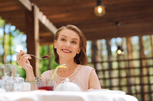 誕生日を祝います。彼女の誕生日を祝っている間非常に幸せを感じている笑顔のブロンドの髪の女性