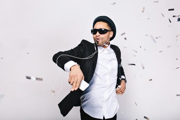 Празднование яркой большой вечеринки возбужденного красивого парня в костюме, шляпе, черных очках, развлекающихся в мишурах. модно смотреться, слушать музыку, танцевать, петь, отдыхать.