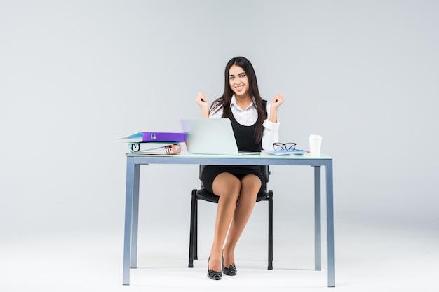 白で隔離のラップトップコンピューターでテーブルに座っている実業家を祝う