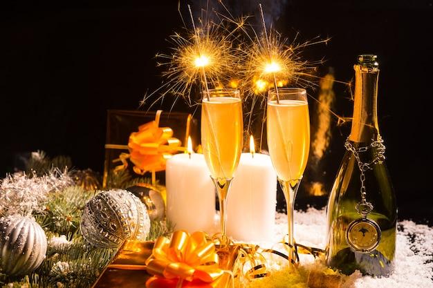 線香花火とシャンパンでクリスマスと新年のお祝いの季節を祝う静物画のキャンドルのギフトと装飾