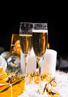 燃えるアドベントキャンドルと豪華な金色の贈り物、コピースペースのある暗い背景で雪の上に立っているロマンチックなシャンパン2杯でクリスマスと新年を祝う