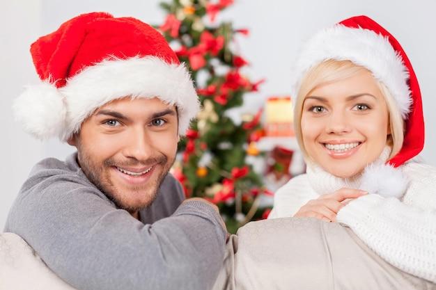 크리스마스를 함께 축하합니다. 소파에 앉아 카메라를 보며 웃고 있는 아름다운 젊은 부부