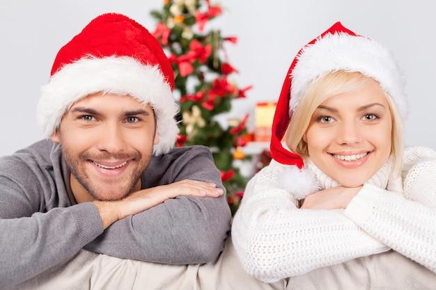 크리스마스를 함께 축하합니다. 쾌활한 젊은 부부는 소파에 앉아 카메라를 보고 웃고