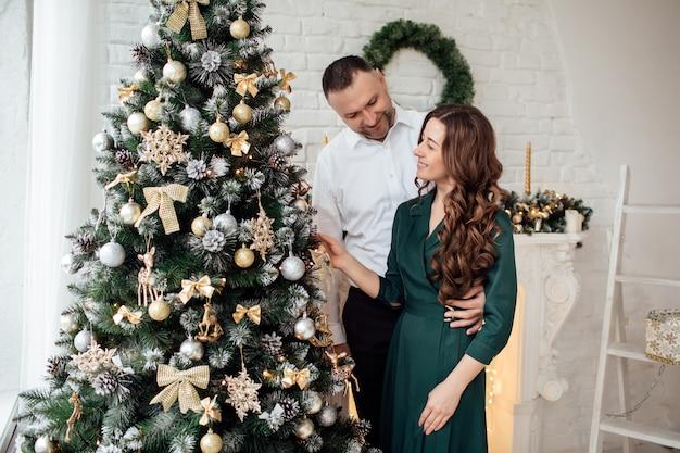 一緒にクリスマスを祝います。クリスマスツリーの近くで抱き締める休日の服を着たカップル。新年