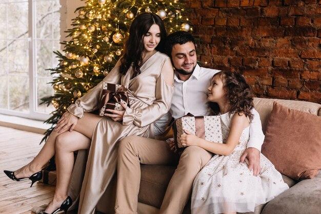 Празднование рождества с семьей возле елки