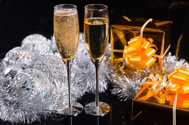 反射する黒い背景の上に銀の装飾品と見掛け倒しを配置したシャンパンと豪華なゴールドギフトの2つのフルートでクリスマスを祝う