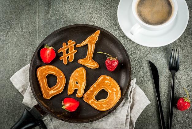Празднование дня отца. завтрак. идея сытного и вкусного завтрака: блины в форме поздравлений - папа №1. в сковороде, кружка кофе и клубника. вид сверху copyspace