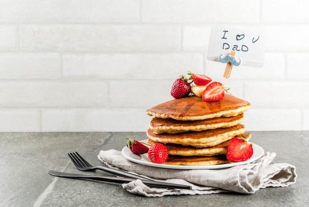 Празднование дня отца. завтрак. идея сытного и вкусного праздничного завтрака: блины с маслом, кленовым сиропом и свежей клубникой, с поздравлениями. чашка кофе. copyspace