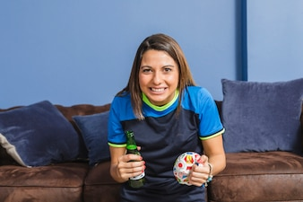 Celebrating female football fan on couch