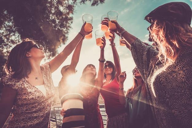 友情または成功チームを祝うことは、色付きのジュースと7人の美しい女性と一緒に屋外で働きます
