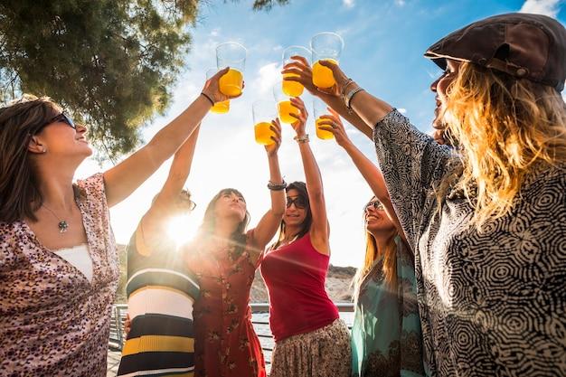 友情または成功チームを祝うことは、色付きのジュースと7つの美しい屋外で働きます