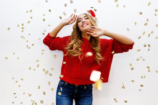 Celebrating girl in santa masquerade hat having fun in confetti on white wall. new ear party mood. cozy red pullover. true emotions. surprise crazy emotions.