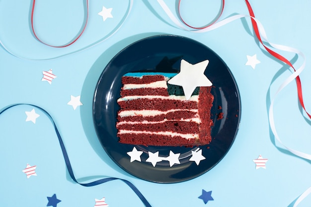 Celebrating independence day, a piece of cake in the form of the usa flag with white, red and blue ribbons and stars on a blue background, close up.