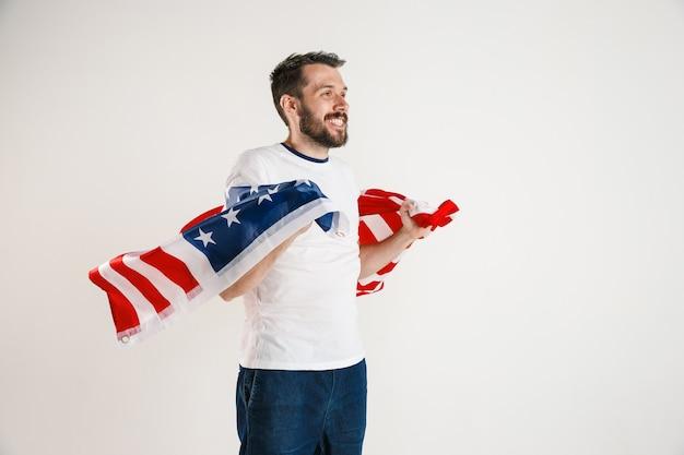 Celebrare un giorno dell'indipendenza. stelle e strisce. giovane con la bandiera degli stati uniti d'america isolato sulla parete bianca dello studio. sembra follemente felice e orgoglioso come un patriota del suo paese.