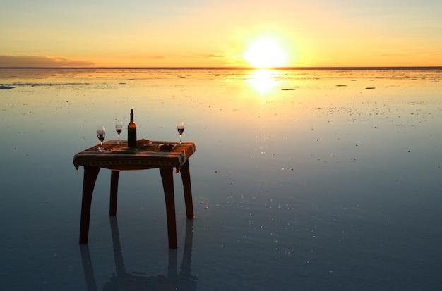 Celebrating on the mirror effect of uyuni salt flats at stunning sunset