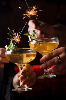 Встреча нового года 2022 года фейерверком с бенгальскими огнями и коктейлями. мята с долькой апельсина в коктейльном бокале, наполненном алкогольными коктейлями.