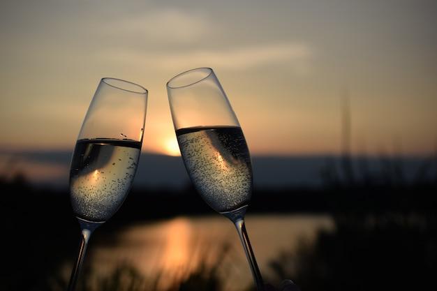 Празднование нового года с двумя бокалами вина на закате у озера с местом для текста