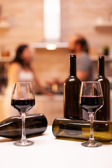 Celebrating relationship with red wine in kitchen