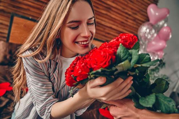 聖バレンタインの日を祝います。男性のトリミングされた画像は、女性に赤いバラを与えます。