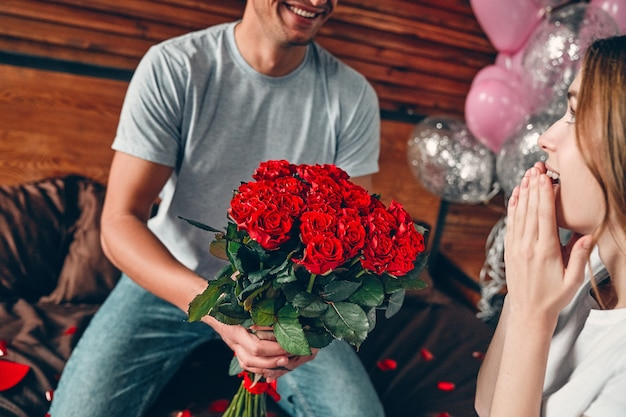 Celebrating saint valentine's day. a man gives a woman red roses. a couple is sitting on the bed with heart-shaped confetti.