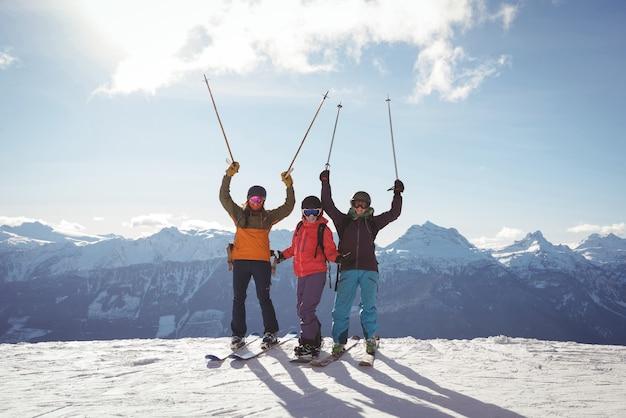 雪に覆われた山に立っているスキーヤーを祝う