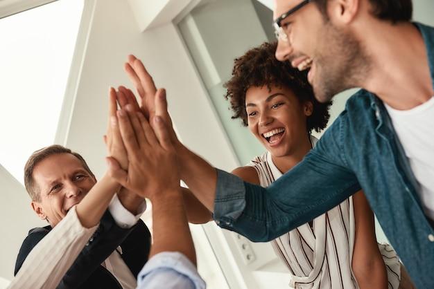 성공을 축하합니다. 현대 사무실에서 함께 일하는 동안 비즈니스 사람들이 서로 하이파이브를 하고 웃고 있습니다. 팀워크