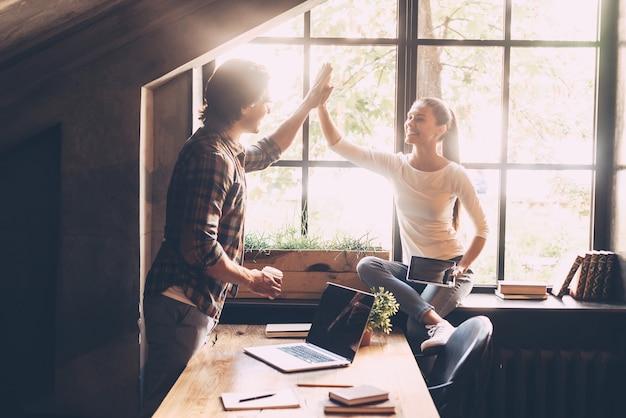 成功を祝う。クリエイティブなオフィスでコーヒーブレイクをしながらハイタッチを与える陽気な若い男と女