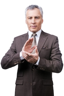 Celebrating success. confident mature man in formalwear clapping hands and smiling while standing against white background