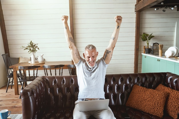 노트북 화면을 보고 키운 캐주얼 옷을 입은 흥분된 중년 남성