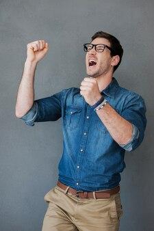 Празднование успеха. взволнованный молодой человек держит руки поднятыми и выражает позитив