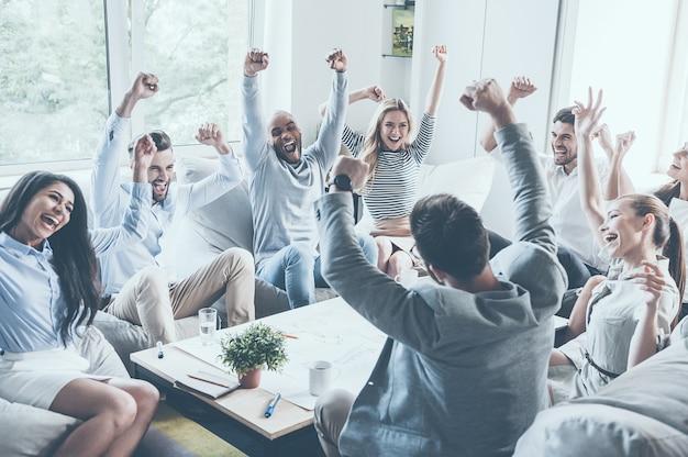 成功を祝う。一緒に机の周りに座って腕を上げて幸せそうに見える若いビジネスマンのグループ