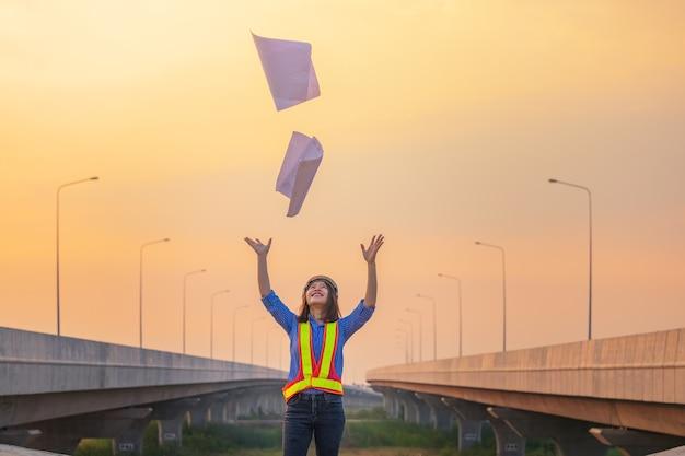 Празднование успеха. счастливая улыбающаяся молодая женщина бросает документы или чертежи и чувствует себя так счастливой, сидя на своем рабочем месте. работать из дома. положительные человеческие эмоции