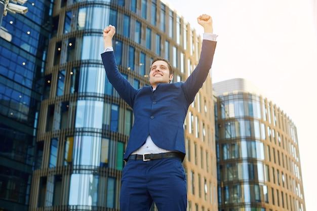 성공을 축하합니다. 사무실 건물을 배경으로 야외에 서 있는 동안 팔을 들고 긍정적인 표현을 하는 흥분한 젊은 사업가의 낮은 각도 보기