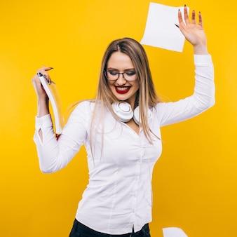 Празднование успеха. портрет молодой и красивой деловой женщины в юбке, подбрасывая документы и улыбаясь пока.