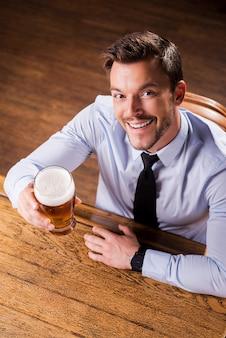 成功を祝う。シャツとネクタイのハンサムな若い男の上面図は、ビールとガラスを保持し、バーのカウンターに座って笑っている