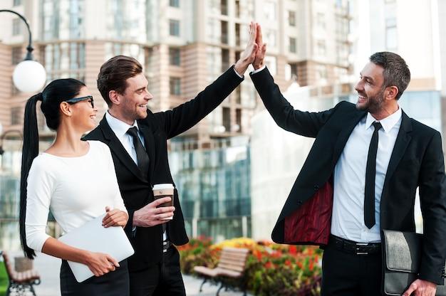 成功を祝う。彼らの女性の同僚がハイタッチを与える2人の幸せな若いビジネスマン