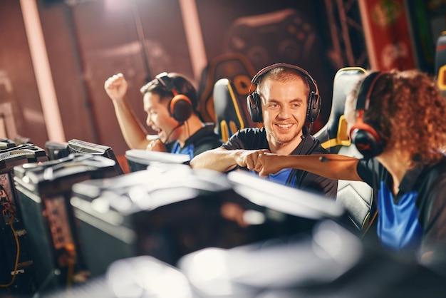 성공을 축하하는 두 명의 젊은 행복한 전문 사이버 스포츠 게이머가 서로에게 주먹을 날립니다.