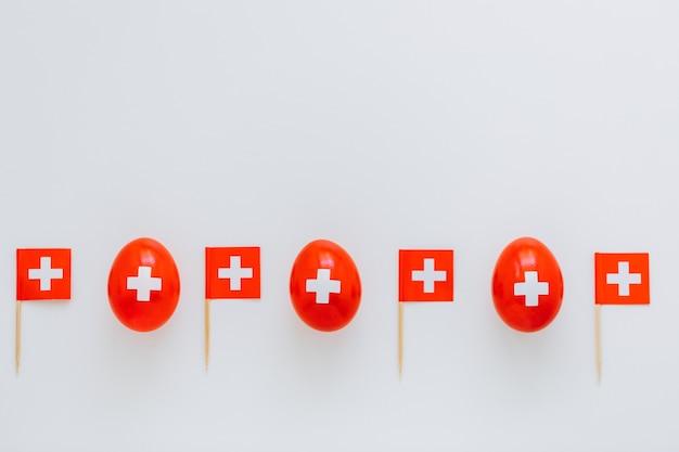 スイスの国旗のような色の伝統的な卵で8月1日にスイスの国民の祝日を祝います。赤い卵とスイスの国旗が並んでいます。