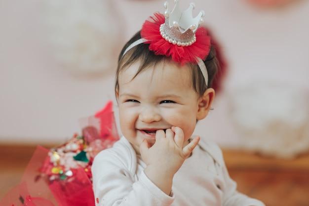 Празднование первого дня рождения. счастливая маленькая принцесса на вечеринке с розовыми девушками