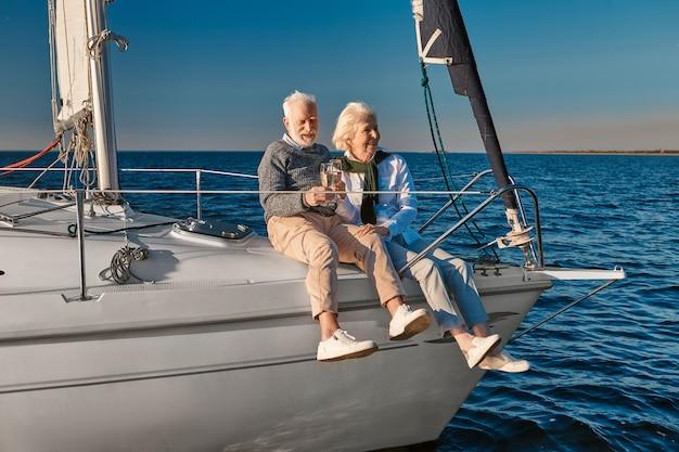 結婚記念日を祝って幸せな年配のカップルがワインやシャンパンを飲みながら笑う