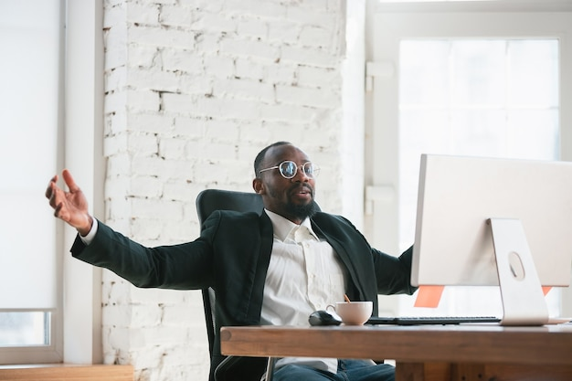 승리를 축하합니다. 아프리카 계 미국인 기업가, 사업가 작업 사무실에 집중. 행복하고 쾌활하며 클래식 한 정장, 재킷을 입고 있습니다. 일, 금융, 비즈니스, 성공 리더십의 개념